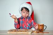 Cute Little Boy Decorating The Gingerbread Cookies