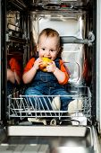 Baby eating apple in dishwasher