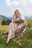 Young woman in dirndl, sitting in nature on a rock