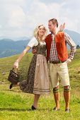 Bavarian couple in fashionable leather pants and dirndl