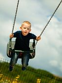 picture of swingset  - Little blonde boy having fun at the playground - JPG