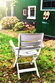 foto of household farm  - Lonely chair in autumn backyard garden. Holland