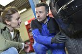 Mechanician showing car wheel wear to client