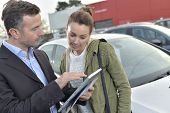 Car dealer showing car specifications to client on tablet