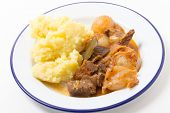 Greek traditional beef stifado, a meat and onion stew, served with mashed potato.