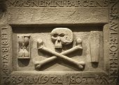 stock photo of skull cross bones  - Skull and cross bones with latin text in a tomb - JPG