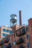 Water Tower On Old Brick Building With Metal Balconies