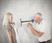 Angry man shouting at girlfriend through megaphone against weathered surface