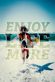 Fit surfer girl running to the sea with her surfboard against enjoy life more