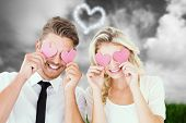 Attractive young couple holding pink hearts over eyes against green grass under grey sky