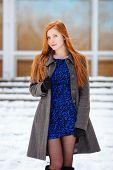 Winter outdoors portrait of young beautiful redhead woman in blue dress and grey coat