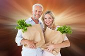Happy couple carrying paper grocery bags against sunrise over mountains