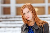 Closeup portrait of young cute redhead woman in blue dress and grey coat at winter outdoors