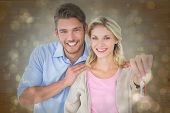 Attractive young couple showing new house key against black abstract light spot design