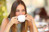 Woman Drinking A Coffee From A Cup In A Restaurant Terrace