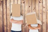 Mature couple wearing boxes over their heads against wooden planks