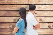stock photo of not talking  - Upset couple not talking to each other after fight against wooden planks background - JPG