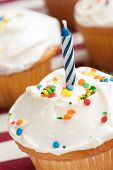 Vanilla cupcake with sprinkles and a blue and white spiral birthday candle on a red and white tablecloth.