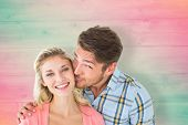 Handsome man kissing girlfriend on cheek against pink and green planks