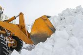 stock photo of bulldozer  - A bulldozer clears snow drifts after the storm - JPG