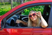 Beautiful Funny Woman In Heart Shaped Glasses In Red Shiny Car Outdoors