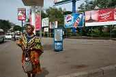 Dark-skinned Tanzanian Woman Stands On Street Surrounded By Outdoor Advertising.