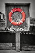 Orange life saver or buoy hanging in wooden box on dock. Prince Edward Island, Canada, selective coloring.