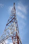 Low angle view of the metal frame of a red and white radio antenna tower against a blue sky background.