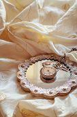 Antique pocket watch on mirror lying on a wedding dress