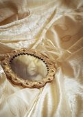 Antique mirror lying on wedding dress