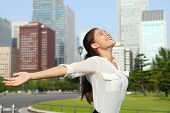 Freedom success businesswoman - Happy free Asian mixed race business woman in Japanese downtown Tokyo city skyline. Carefree young adult arms open up in the sky, Japan.