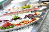 stock photo of buffet  - Salad buffet bar under natural light with shallow depth of field - JPG