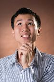 Young Chinese frank businessman thinking, closeup portrait in studio.