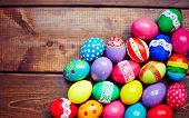 Creative Easter eggs of different colors on wooden background