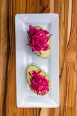 pic of fermentation  - serving of fermented or cultured purple cabbage paired with an avocado on a white plate - JPG