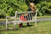 picture of sitting a bench  - Single blonde woman sitting on the wooden bench into the nature - JPG