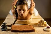 image of therapist massage  - The beautiful girl has Thai massage. Beautiful setup - towels, candle, frangipani flower and stones