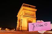 Composite image of hand holding card showing je taime against arc de triomph