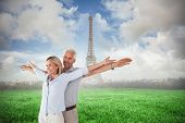 Happy couple standing with arms outstretched against eiffel tower