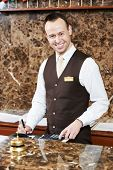smiling male receptionist passing key card to guest