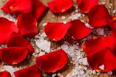 Red roses petals with pile of salt on old wooden board