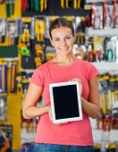 Portrait of confident woman showing digital tablet in hardware shop