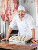 Portrait of confident mature butcher leaning on table in butchery