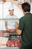 Happy female butcher selling meat to man in shop