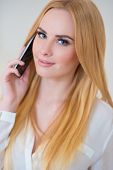 Close up Pretty Woman with Long Blond Tied Hair  Wearing White Long Sleeve Shirt  Calling Through Mobile Phone While Looking at the Camera. Isolated on Off White Background.