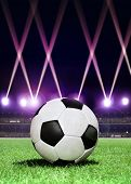 soccer ball in the center of stadium during festive lighting at evening