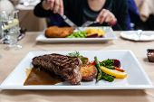 picture of strip  - A delicious strip loin beef steak meal served with fresh vegetables and marsala portobello mushroom sauce. Deliberate shallow depth of field on subject having a meal across the table.