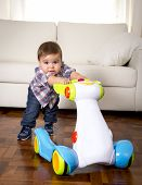stock photo of scared baby  - sweet little one year old boy walking alone with baby walker taking his first brave steps at home in living room excited and playful in childhood and growth concept - JPG