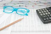 Blue Spectacles Brown Pencil And Calculator On Finance Account