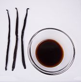 foto of vanilla  - Three Vanilla Beans Laid on a White background with a clear bowl of vanilla extract - JPG